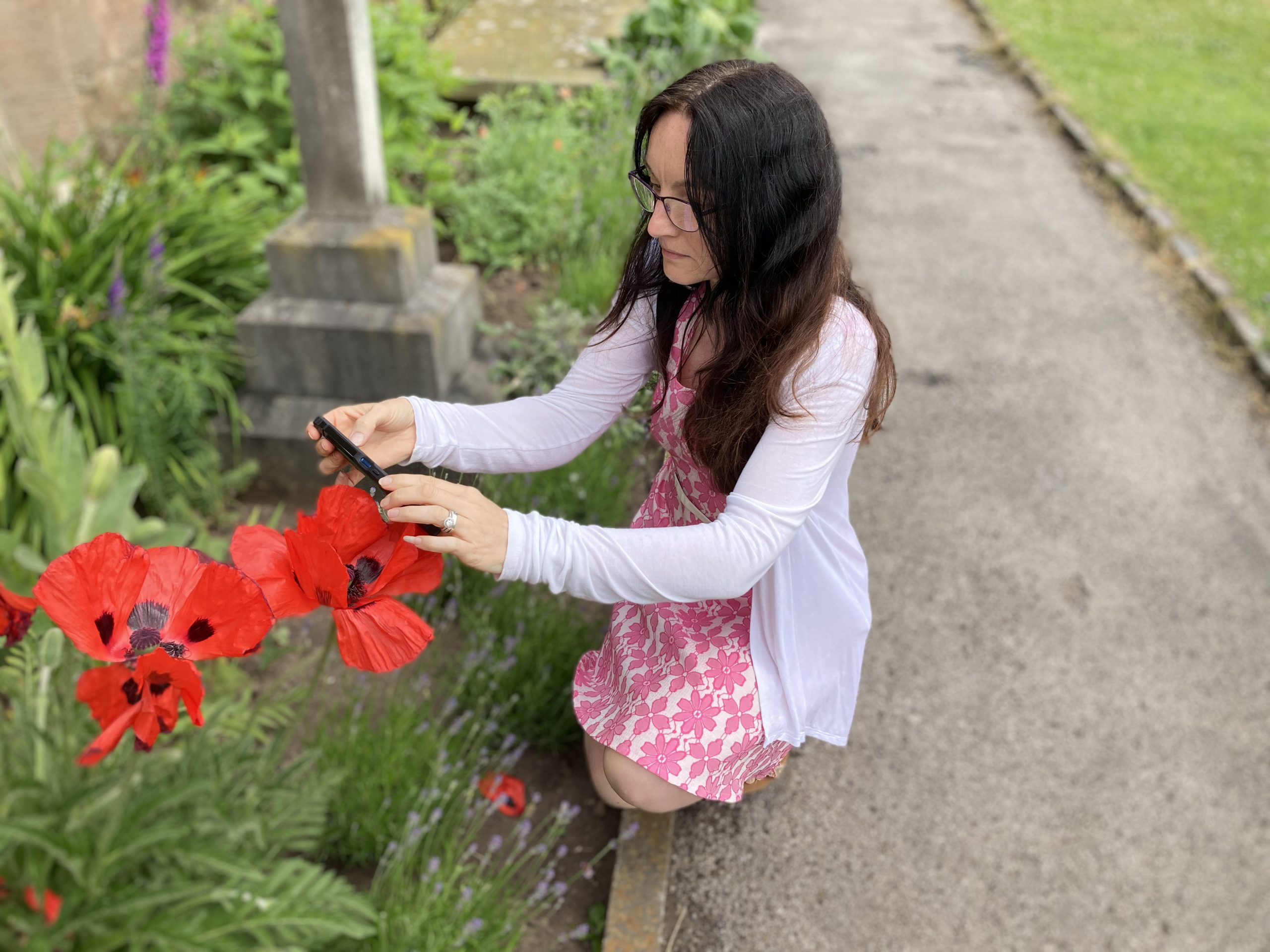 Ruth bending down taking a photo of a flower.